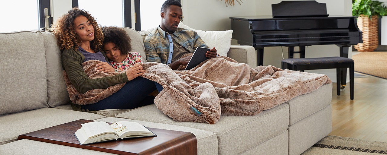 Family enjoying some time together while snuggled in their Lovesac Footsac.