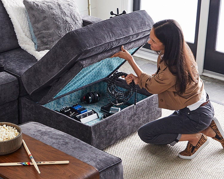 Woman storing items in her Lovesac Storage Seat.