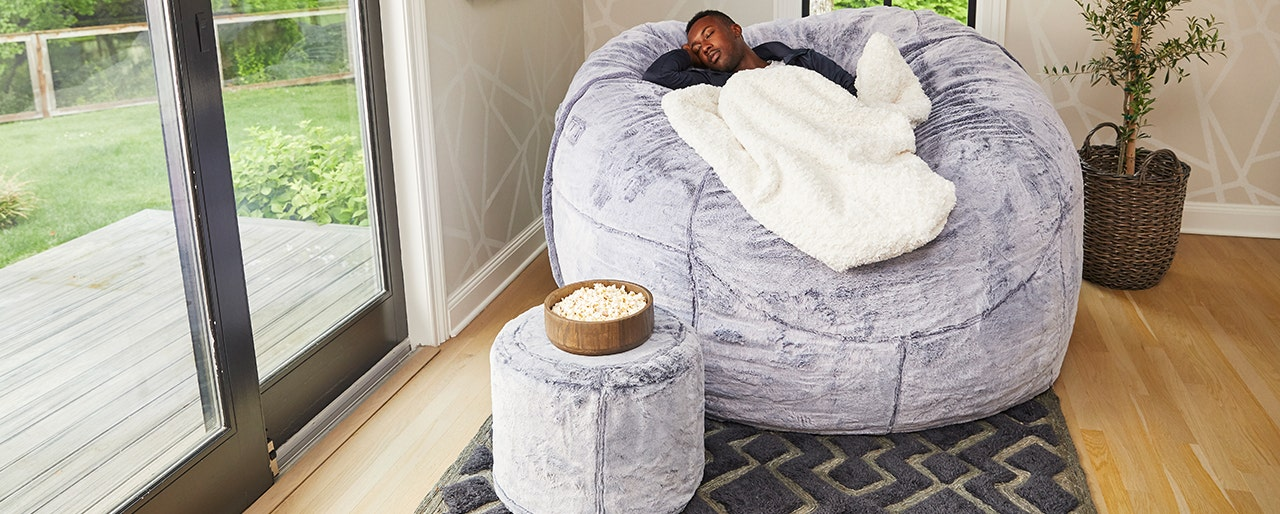 Man napping in a comfortable Lovesac beanbag.