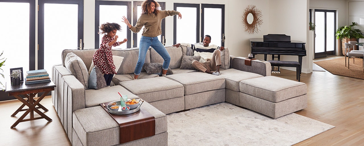 Family having fun and jumping on their Lovesac Sactional.