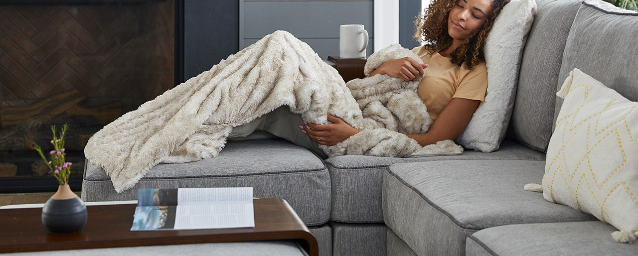 Woman cuddled up and covered with a comfortable blanket.