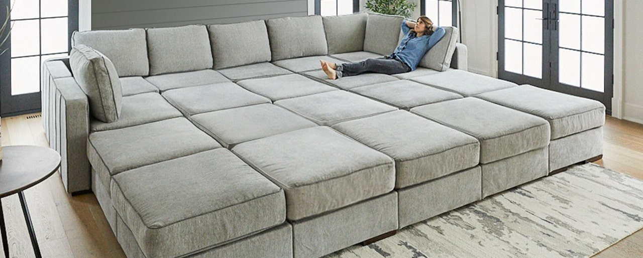 A woman relaxing in a huge sactional couch configuration.