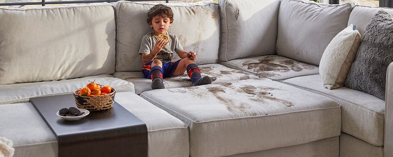 Little kid enjoying a cookie after covering the couch with mud.