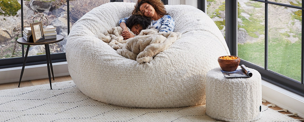 Woman and a baby cuddled up and napping on a comfortable bean bag.