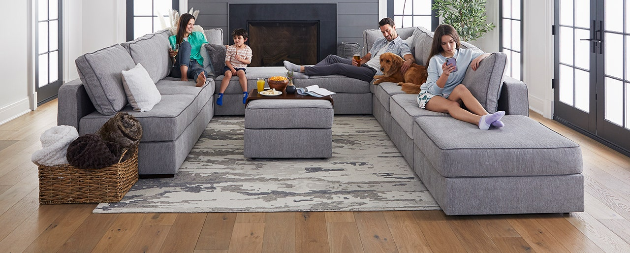 Parents relaxing with their kids and dog in a living room.