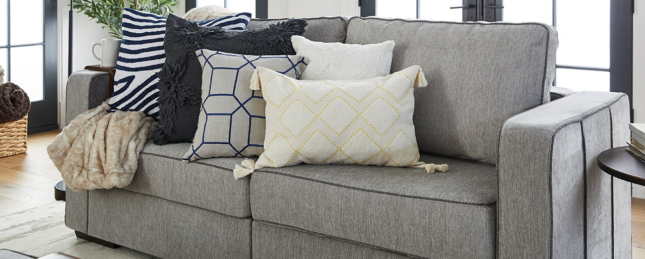Beautiful decorative throw pillows on a Lovesac couch.