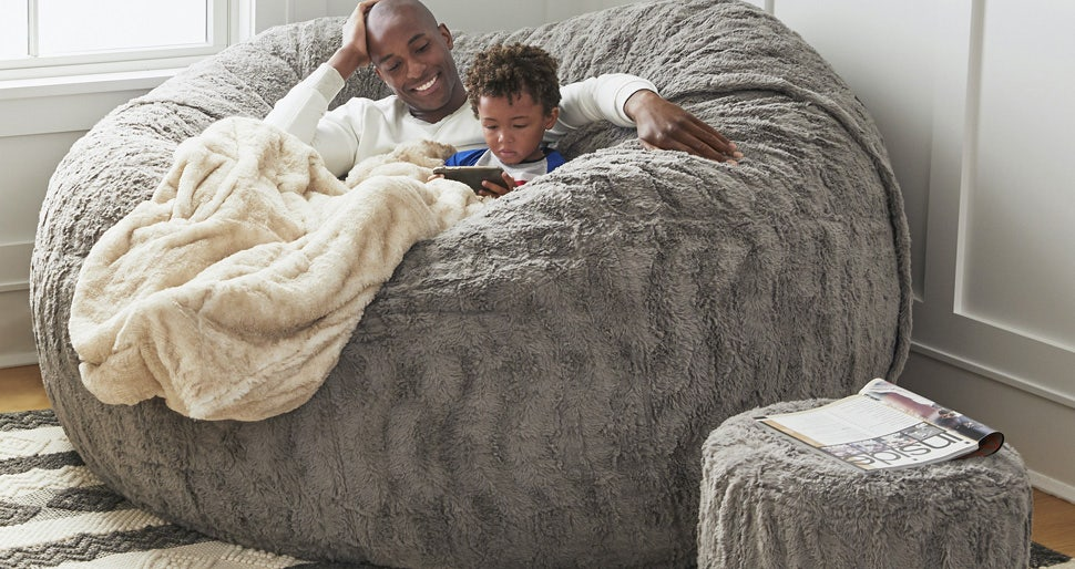 A father and son cuddling in a BigOne Sac with a Footsac blanket