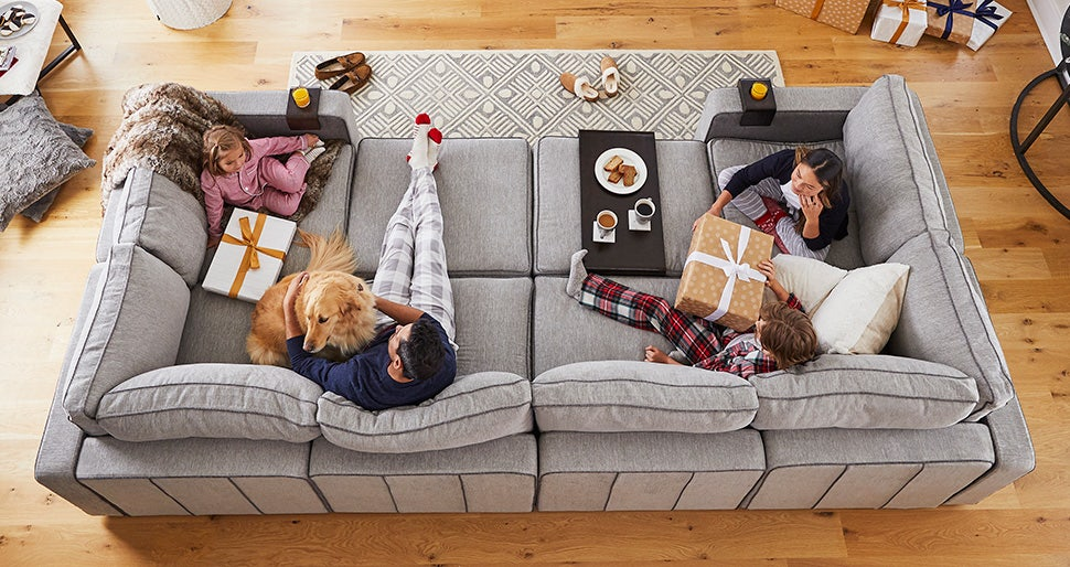 An overhead view of a man and woman on the couch with wrapped gifts