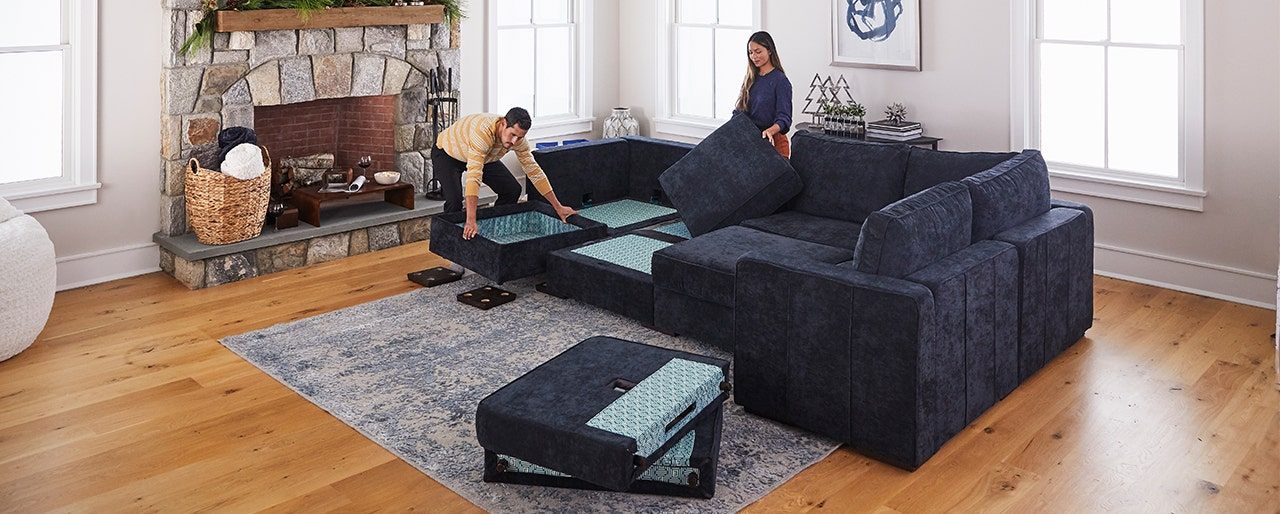 A man and a woman assembling a couch