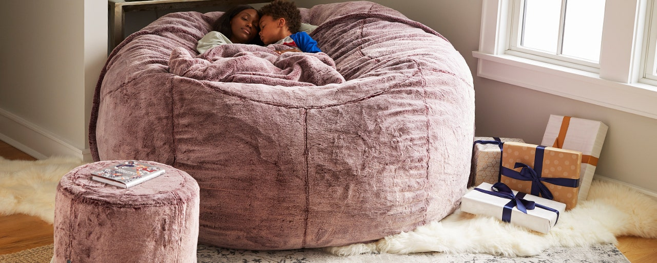 Woman and child relaxing in a light purple beanbag