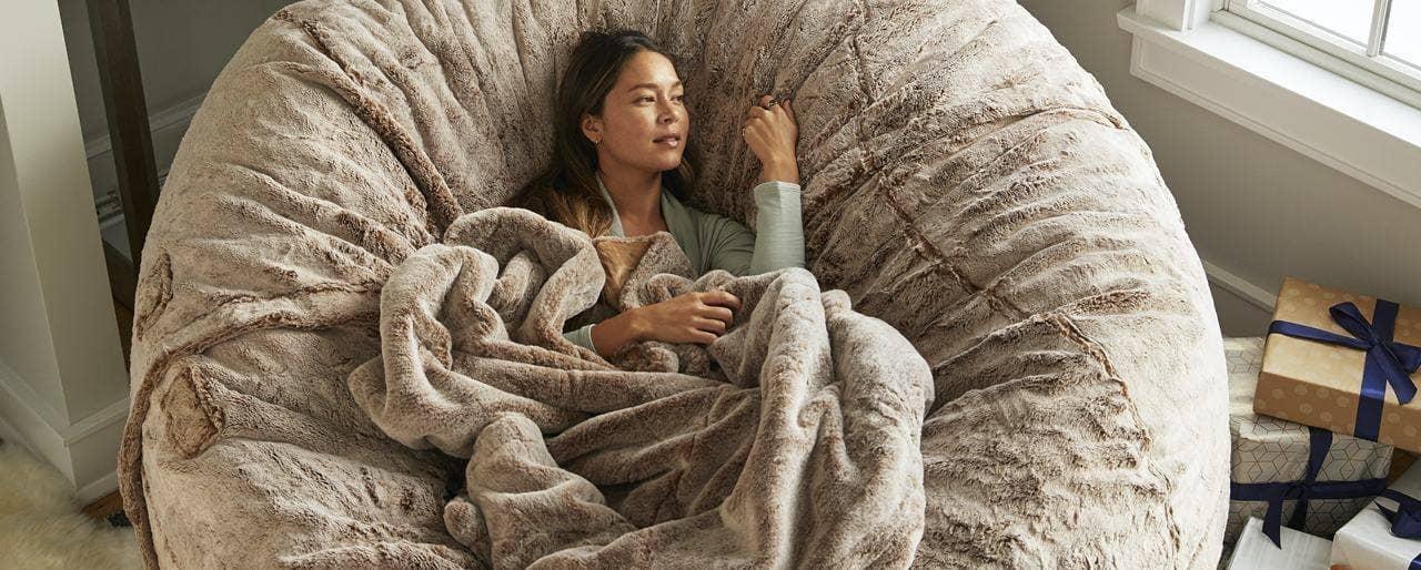A cozy girl sitting in a BigOne Sac with a Footsac Blanket