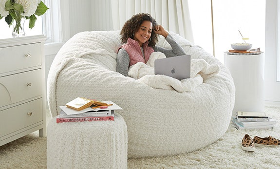 A girl sitting on a BigOne Sac with her laptop and a Footsac blanket.