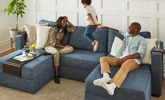 A mother and father sitting on Sactionals with their son jumping on the couch.