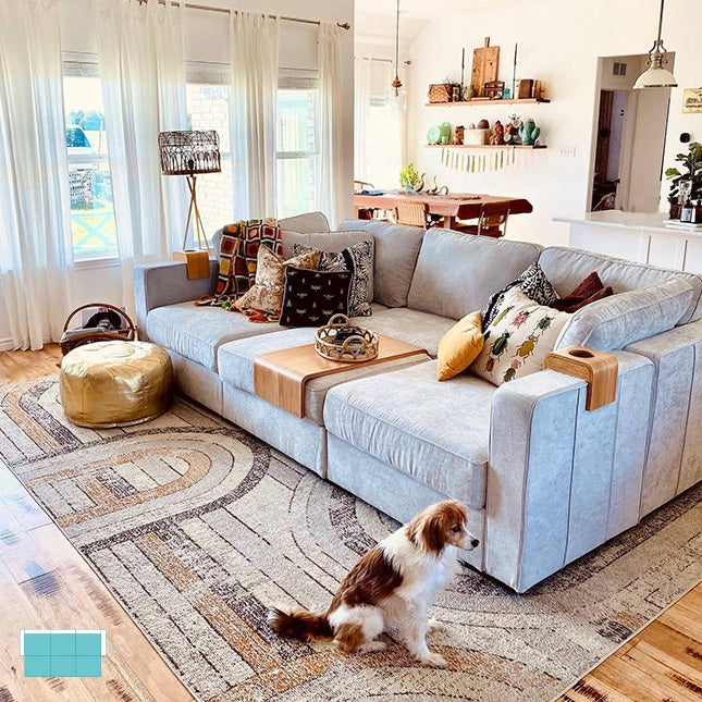 Living room with a large sactional couch set-up and a dog on the side.