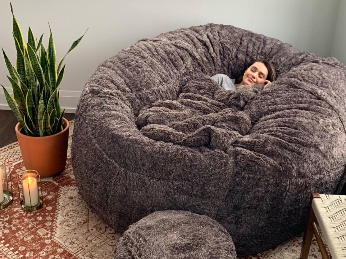 Woman cuddled up on a beanbag/ sac.
