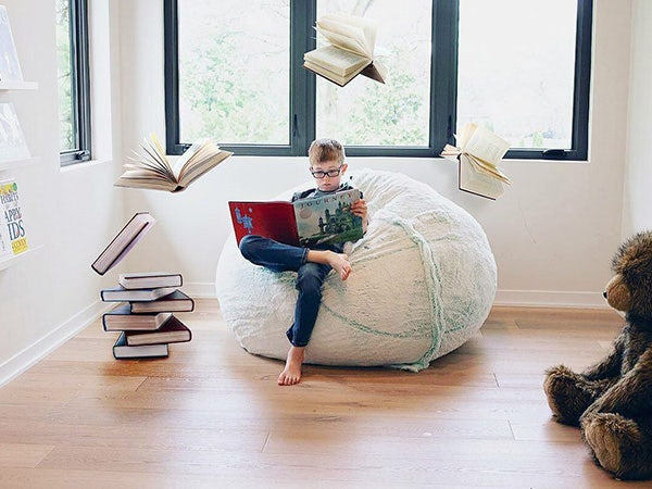 Boy sitting on a beanbag reading a book