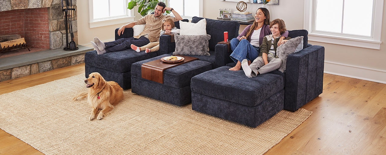 Family of four relaxing in a living room with their dog.