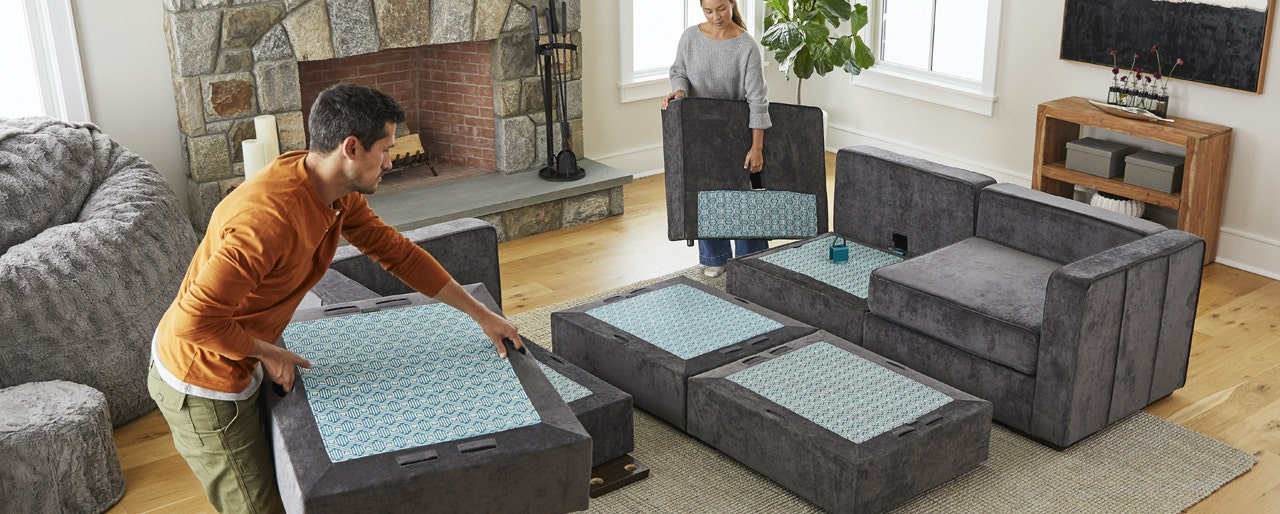 Man and women setting up grey couch