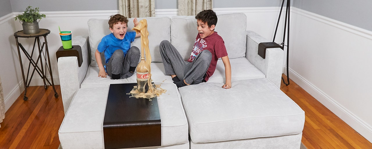 Two boys making a mess on the couch with a mentos and Diet Coke experiment.