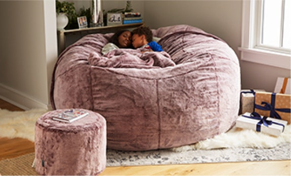 A mom and her son cuddling in a BigOne Sac with a Footsac blanket