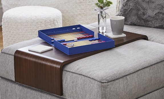 A backgammon game, coasters, and a mug on a Sactionals Table