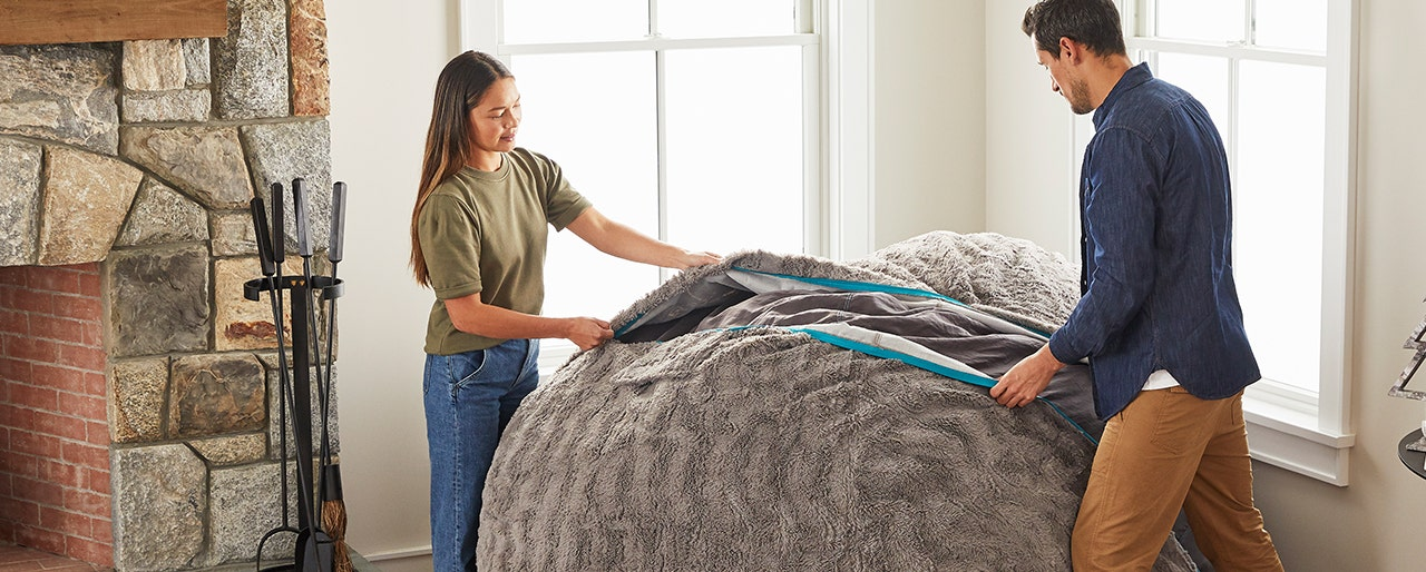 A woman and a man putting a cover on a BigOne Sac.