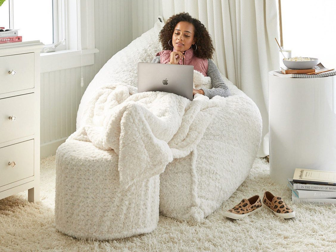 A girl sitting in a PillowSac looking at her laptop