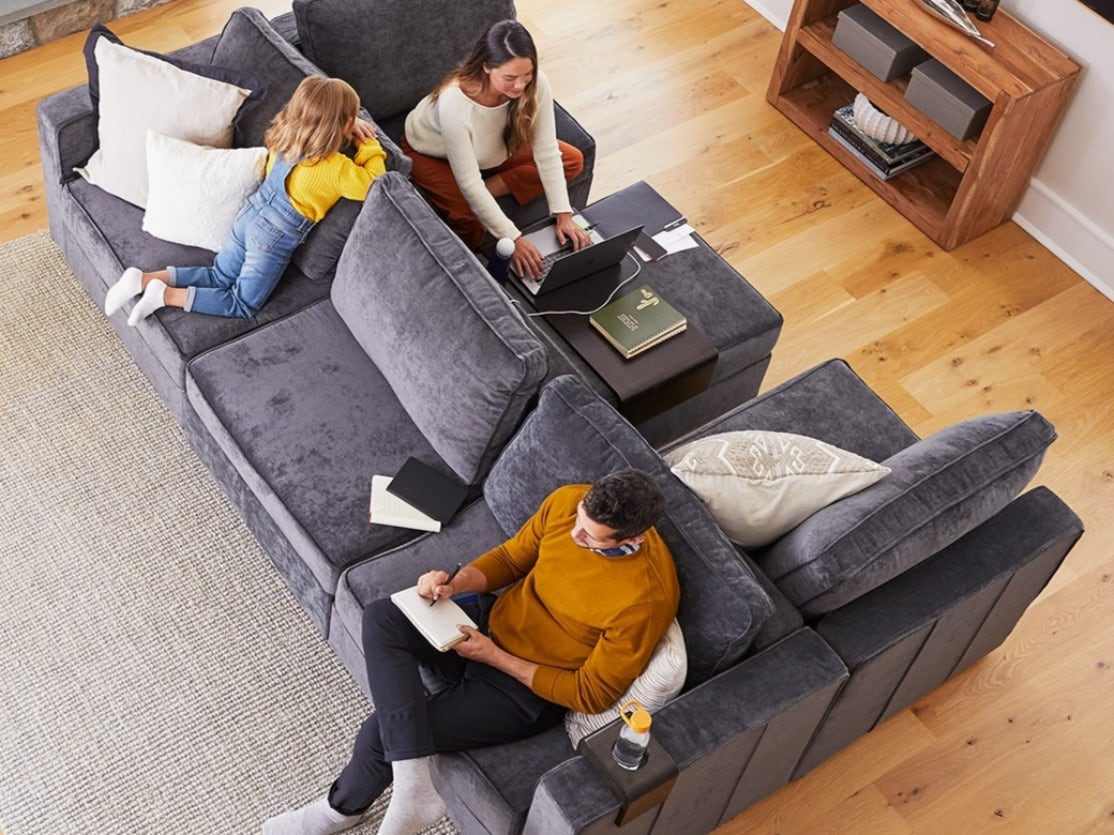A family relaxing on their large sactional / sectional couch
