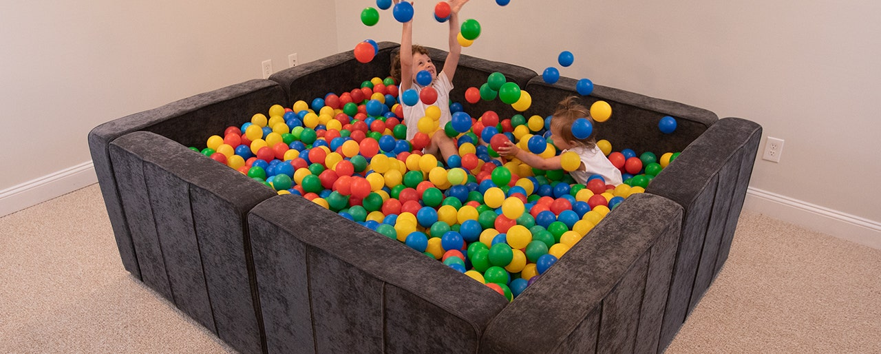 Two children playing in a ball pit made with Sactionals