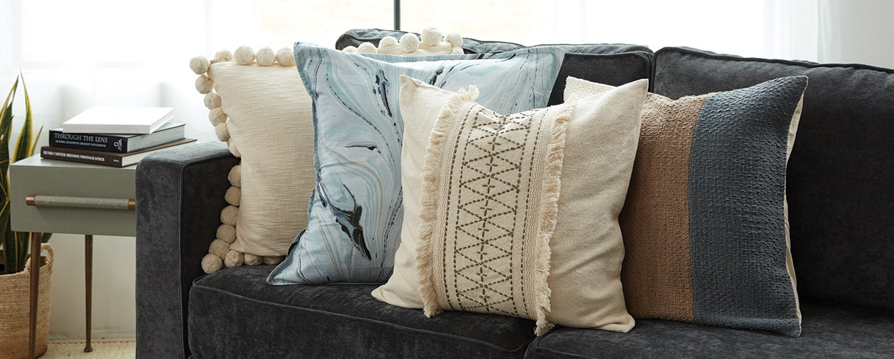 Four decorative throw pillows on a couch