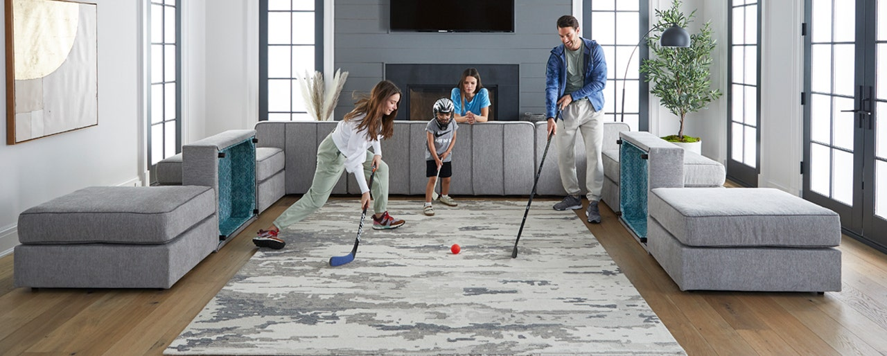 Family in living using Lovesac Sactionals to play hockey.
