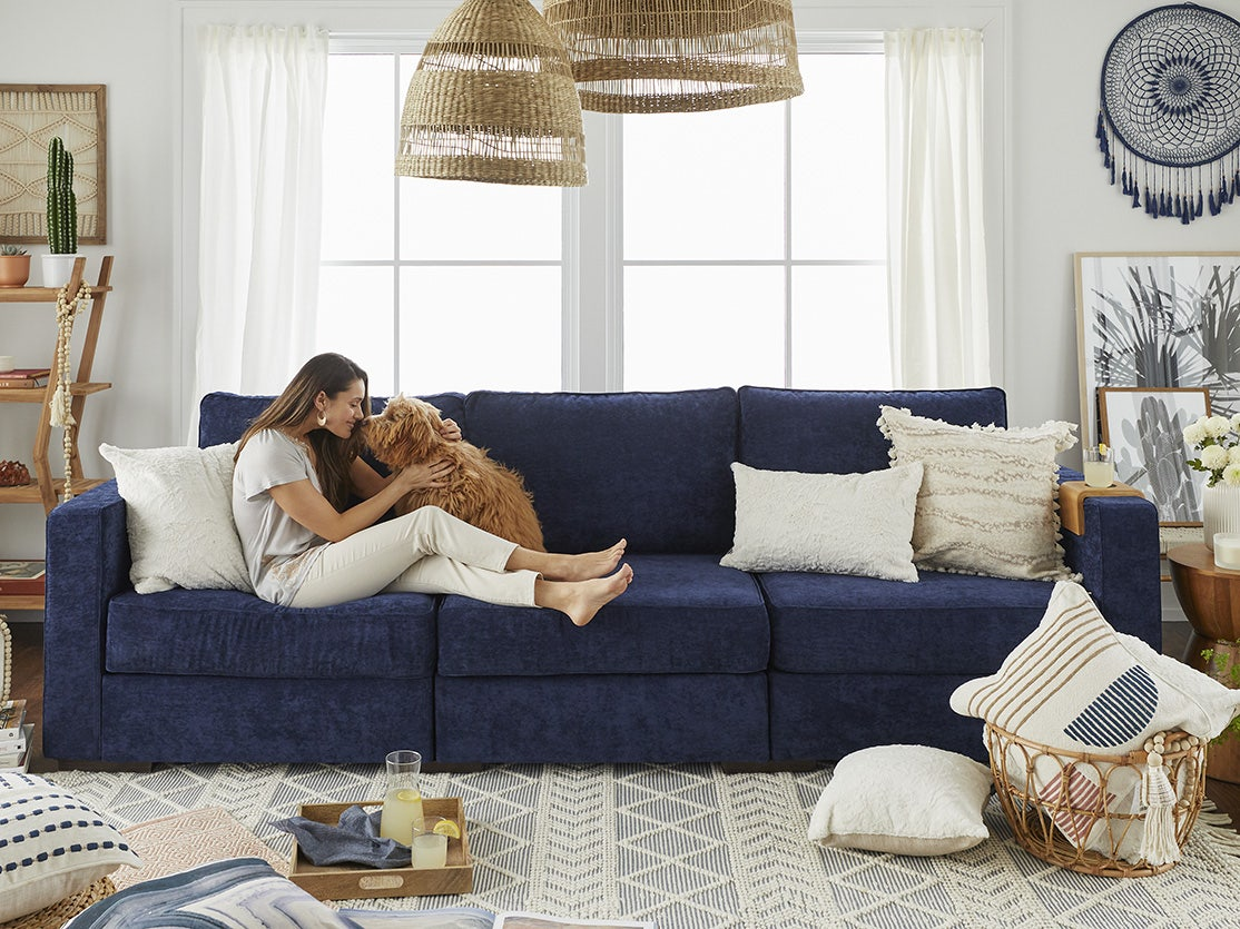 A woman and her dog cuddling on a Sactionals couch