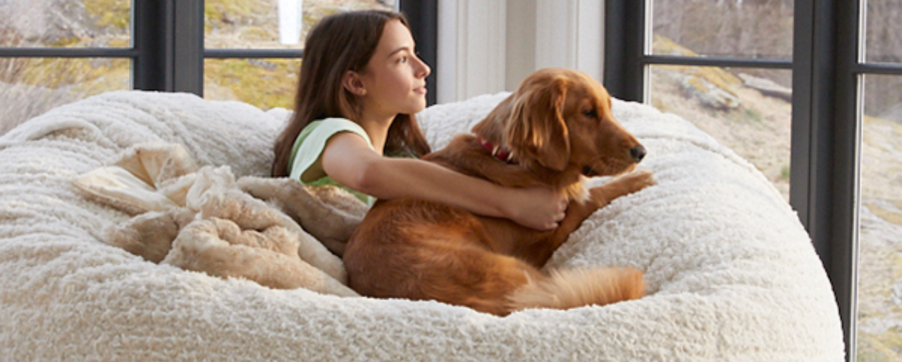 Girl and her dog happily relaxing in a Lovesac beanbag.